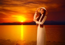 Young vietnamese woman on sunset background.